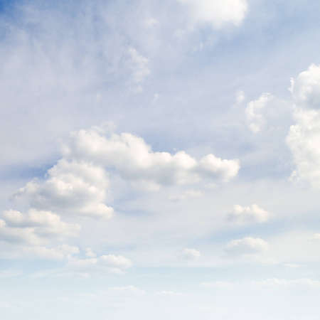 rainclouds: white fluffy clouds in the blue sky                                     Stock Photo