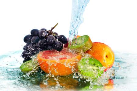 Fruits dans un jet d'eau isolé sur un fond blanc Banque d'images - 12740121