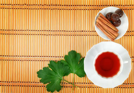 Hot tea with spices on a bamboo mat background                                     photo