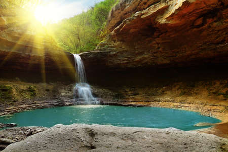 Waterfall in the mountains illuminated by the sun Stock Photo - 15120521