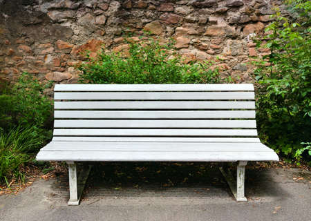 bench: Wooden bench near a stone wall