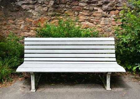 garden bench: Wooden bench near a stone wall