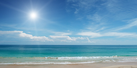 Sandy beach and sun in blue sky Standard-Bild