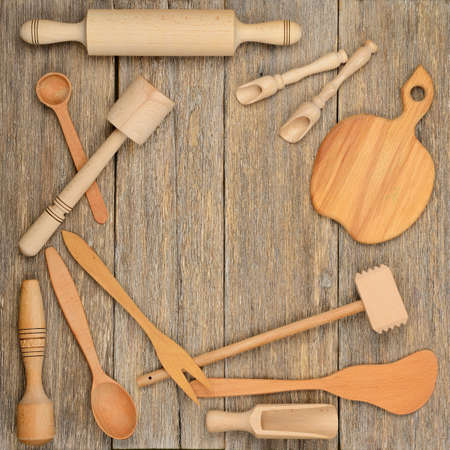 Kitchen wooden utensils (spoon, plate, fork, pestle) on a table made of planks. Top view