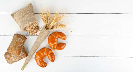 Bread products, ears of wheat, croissants, ciabatta on a white wooden background. Copy space. Top view.