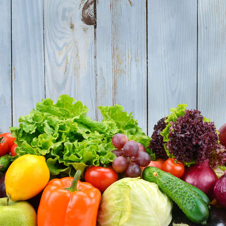 Vegetables and fruits on light blue wooden wall background. Healthy foods.