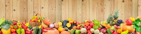 Panoramische foto gezonde groenten en fruit tegen lichte houten muur. Vrije ruimte voor tekst.