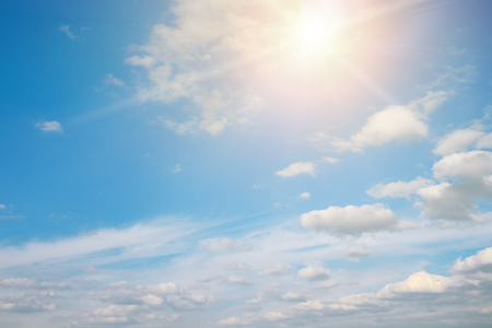 Bright sun against blue sky and white clouds. Copy space