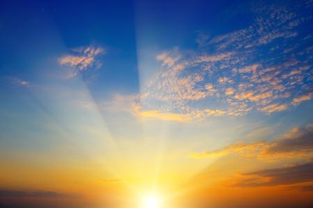 Puesta de sol escénica con rayos de sol contra el cielo azul brillante y nubes naranjas Foto de archivo