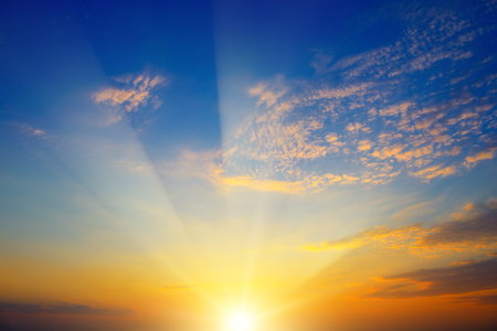 Scenic sunset with sun rays against bright blue sky and orange clouds