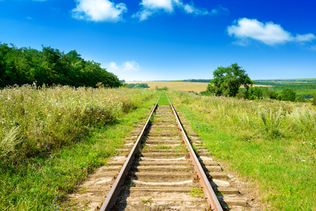 Old railway track among summer fields.