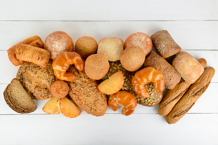 Bread, buns, croissants and other baked goods on wooden table. Top view. Copy space