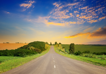 Sunrise over picturesque landscape. Straight road and fields illuminated rays sun.