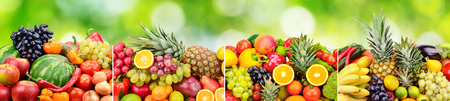 Panoramic skinali from bright fresh vegetables, fruits, berries on green natural blurred