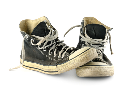 Old faded and worn sneakers isolated on white