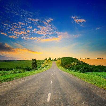 Sonnenaufgang über malerischer Landschaft. Gerade Straße und Felder beleuchteten Strahlen Sonne.