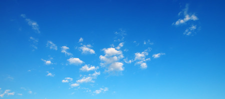 Small fluffy clouds on bright blue sky