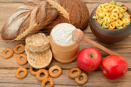 Tasty and healthy products and breads on wooden table
