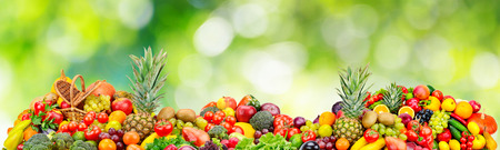 Large pile healthy fruits and vegetables on natural blurred green