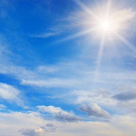 Strahlende Sonne und weiße Wolken am Himmel Standard-Bild