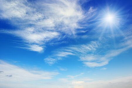 Bright sun on blue sky with white clouds Stock Photo