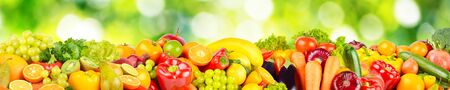 Isolated on green blurred background fruits and vegetables. Copy space