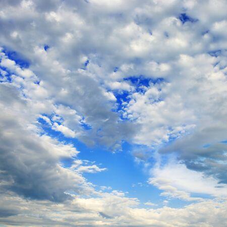 Fluffy white cumulus clouds against blue sky.