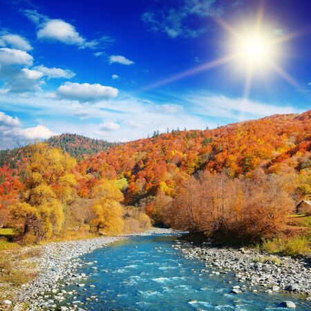 Bright autumn landscape of mountain river valley with bright sun. Stock Photo