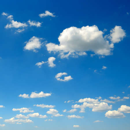 White fluffy clouds on blue sky background.