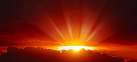 Majestic sunset with bright sunbeams on red sky.