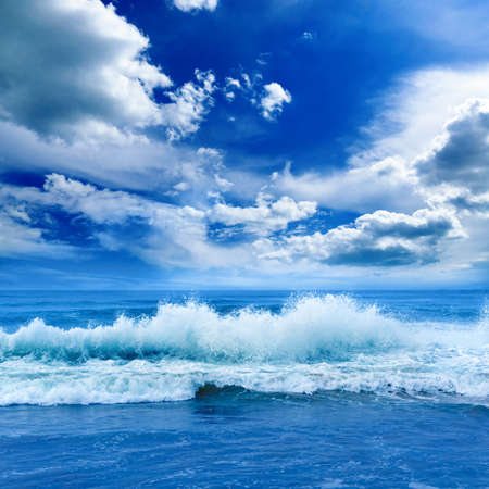 Bright ocean landscape in blue tones. Sea waves and beautiful sky with white clouds.