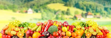 Ripe vegetables and fruits on background of rural landscape Stock Photo