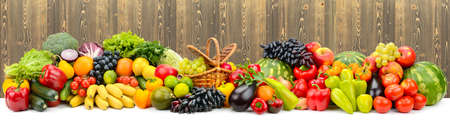 Panoramic collage of ripe, juicy fruits, berries and vegetables on wooden background. Foto de archivo