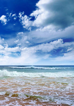 Vertical bright seascape with white clouds, blue sky and beautiful sea surf.