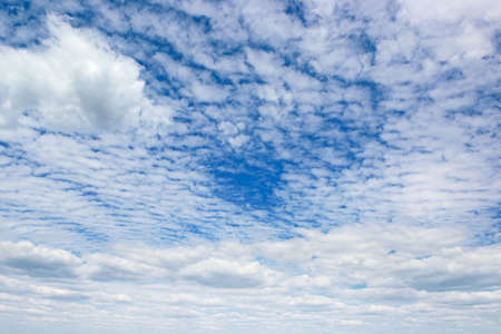 Rectangular landscape with blue sky and white clouds.