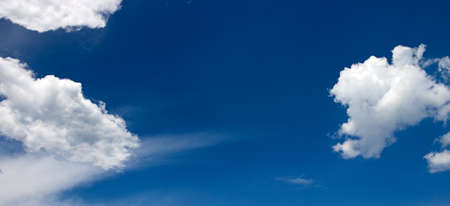 White clouds against background of bright blue sky. 版權商用圖片