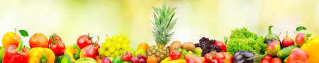 Fresh fruits and vegetables with large pineapple on green blurred background.