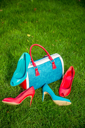 two pairs of green and red shoes and bag lay on the grass photo