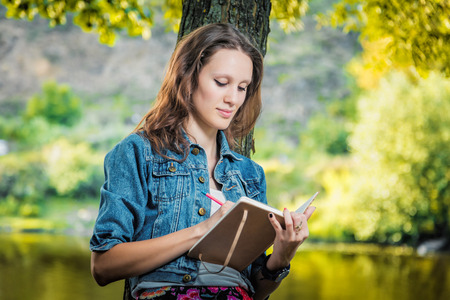 student looking in a notebook in a park near the river University photo