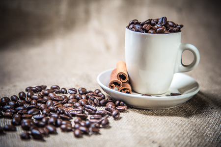 cup of coffee beans on sackcloth
