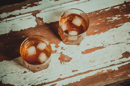 Two glasses of whiskey vintage photo, a bottle bar on wooden rack photo