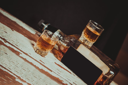 Two glasses of whiskey standing on the bar near the bottle photo