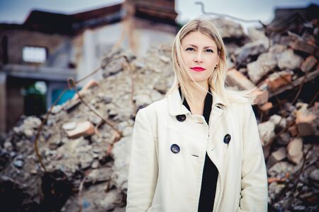 house coat: Blonde in the coat on the ruins of the house, beauty fashion Stock Photo