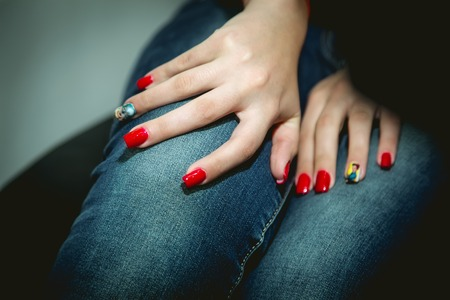 hand care: Red manicure, manicured hands, jeans