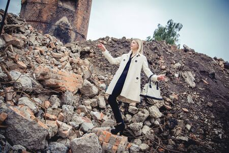 house coat: Blonde in the coat on the ruins of the house Stock Photo