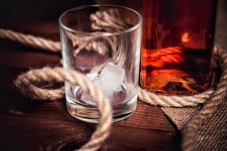 whisky glass: Whisky glass with ice, a bottle of whiskey Stock Photo