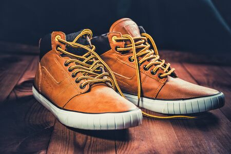yellow men's shoes on a wooden background