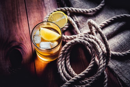 A bottle of whiskey, rum, brandy, lime on a wooden background Stock Photo