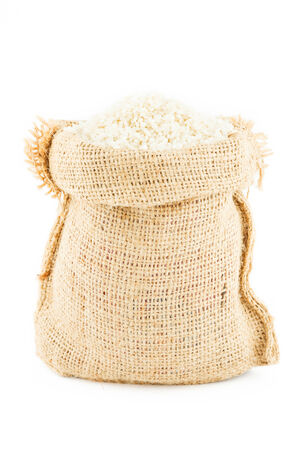 a linen sack filled by rice isolated on a white background photo