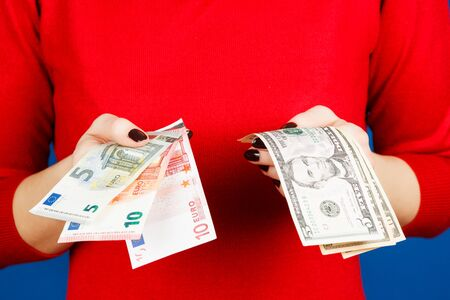 dolar: euro and dolar in the hands of a girl in a red sweater on a blue background